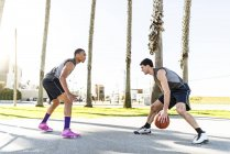 Young men playing basketball on ground — Stock Photo
