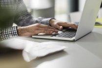 Hombre joven usando el portátil en el escritorio en la oficina - foto de stock