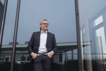 Успешный бизнесмен, стоящий на офисной террасе, выглядит довольным — стоковое фото