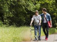 Feliz abuelo caminando con su nieto en la naturaleza - foto de stock