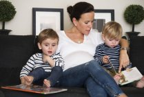 Mother reading book with her sons sitting on sofe — Stock Photo