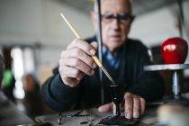 Старший чоловік лицювальні керамічні у вільний час — стокове фото