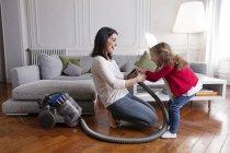 Madre e hija poco divertirse con aspiradora en la sala de estar - foto de stock