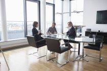 Trois femmes d'affaires ayant la réunion dans le bureau moderne — Photo de stock