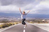 Junge Frau springen vor Freude auf einer Straße — Stockfoto