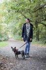 Femme marche avec chien sur le chemin dans la nature — Photo de stock