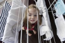 Portrait of little girl standing under a drying rack — Stock Photo