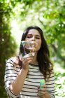 Young woman blowing soap bubbles — Stock Photo