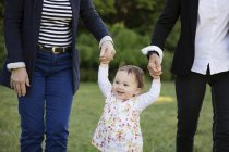 Smiling toddler girl holding hands of grandmothers while walking — Stock Photo