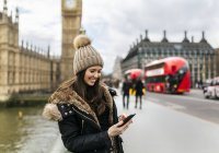 Souriante jeune femme UK, Londres, regardant son smartphone devant le Palais de Westminster — Photo de stock