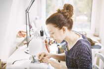 Young woman working on sewing machine — Stock Photo