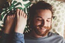 Retrato de jovem sorridente deitado além de pés de namorada — Fotografia de Stock