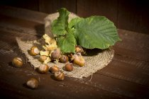 Nocciole e foglie su tela di sacco su superficie di legno marrone — Foto stock