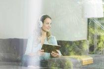 Улыбающаяся женщина дома на диване с цифровыми планшетами и наушниками — стоковое фото