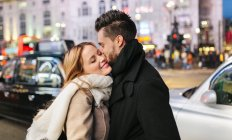 Young man kissing girlfriend on street in London, United Kingdom — Stock Photo