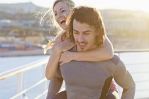 Young man giving his girlfriend a piggyback ride on deck of a cruise liner — Stock Photo