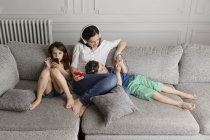 Mother and her children sitting on the couch listening music with their headphones and smartphones — Stock Photo