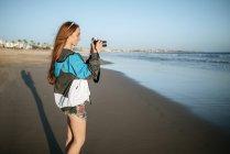 Souriante jeune femme à l'aide d'une caméra sur la plage — Photo de stock