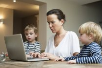 Mother using laptop with her sons sitting next to her — Stock Photo