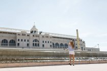 Spain, Barcelona, Young woman in front of train station — Stock Photo