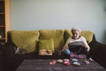 Crochet femme âgée assise sur le canapé en plus de ses chats endormis — Photo de stock