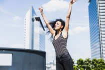 Enthusiastic young woman raising her arms outdoors — Stock Photo
