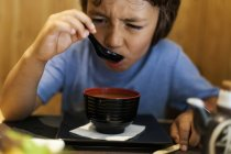 Little boy sitting in an Asian restaurant eating hot miso soup — Stock Photo