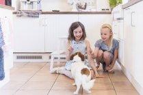 Дві дівчинки, викладання собака кухні — стокове фото