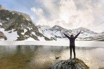 Woman standing with raised arms at mountain lake, Spain, Asturias, Somiedo — Stock Photo