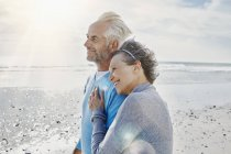 Happy couple on the beach looking at the sea — Stock Photo