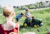 Enfants jouant avec tracteur jouet — Photo de stock