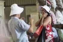 Casal compras juntas para chapéus no brechó — Fotografia de Stock