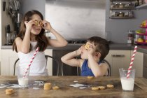 Little girl and boy covering their eyes with cookies — Stock Photo