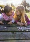 Маленькі дівчатка, лежачи на boardwalk з ромашки і дивляться один на одного — Stock Photo
