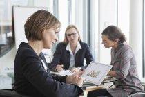 Empresaria con tableta digital en una reunión - foto de stock