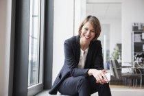 Mulher de negócios sorridente sentada à janela e olhando para a câmera — Fotografia de Stock