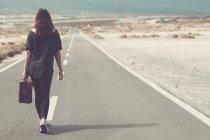 Mujer joven con maleta caminando por un camino - foto de stock