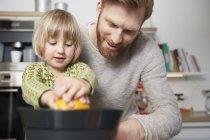 Padre e figlia utilizzando spremiagrumi in cucina — Foto stock
