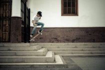 Teenage boy on skateboard jumping on stairs — Stock Photo