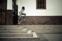 Adolescent sur planche à roulettes, sauter dans les escaliers — Photo de stock