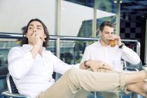 Two young men smoking and drinking beer on cruise ship — Stock Photo