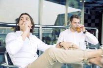 Двое молодых людей, курить и пить пиво на круизное судно — стоковое фото
