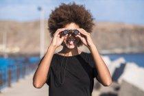 Giovane donna sorridente con binocolo — Foto stock
