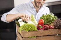 Молода людина з дерев'яний ящик з свіжих овочів і двох пляшок молока — стокове фото