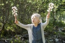 Blond little girl holding umbels in her hands — Stock Photo