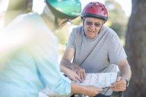 Pareja mayor con mapa en bicicletas - foto de stock