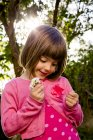 Портрет маленькой девочки, держащей маргаритки на улице — стоковое фото