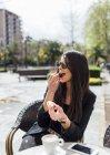 Jolie jeune femme buvant café au café de la chaussée — Photo de stock