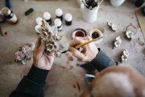 Hombre mayor decorando cerámica en su tiempo libre - foto de stock