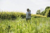 Agricultor segurando enxada no campo de estupro — Fotografia de Stock